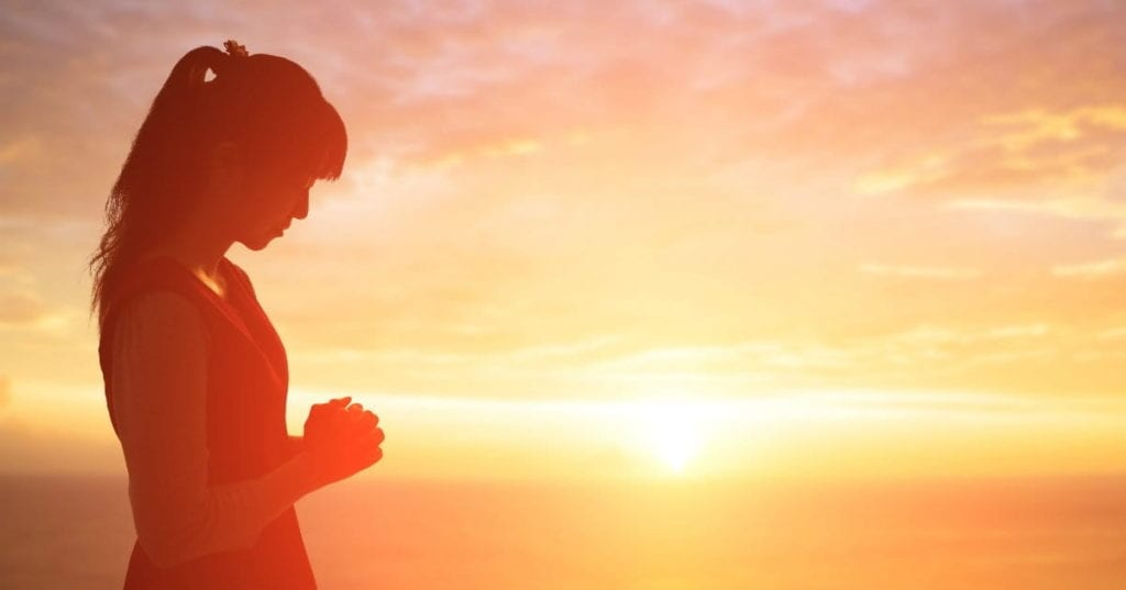 women in prayer at sunset