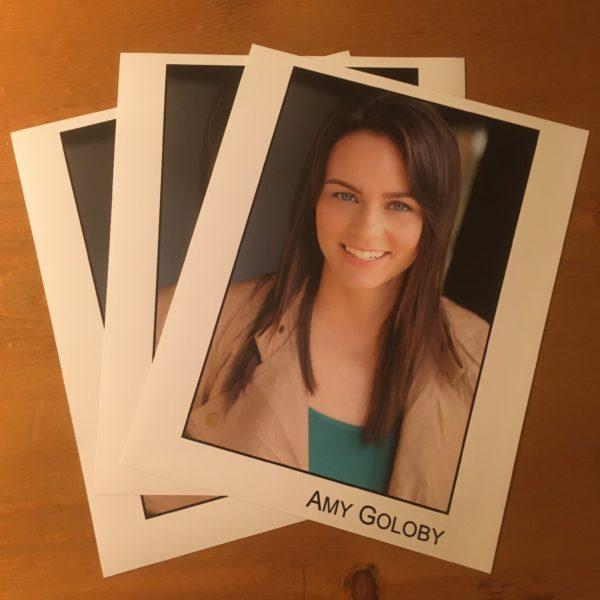 headshot Amy Goloby beige jacket green tank top brunette woman